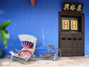 En solblekt trishaw är stor kontrast mot den djupt blå väggen